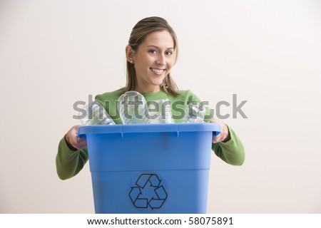 An attractive young woman his smiling and holding a blue recycle bin with plastic bottles in it. Horizontal shot. - stock photo