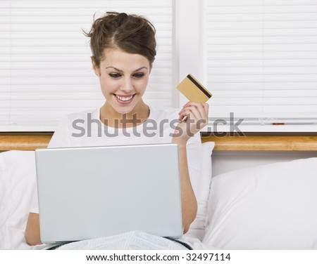 An attractive young woman holding a credit card while using a laptop.  She is smiling at the laptop screen.  Horizontally framed shot. - stock photo