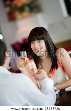 An attractive young woman holding a glass of white wine and smiling at her partner at a restaurant