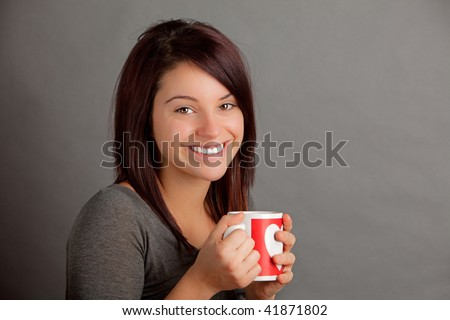 An attractive young woman holding a warm cup of coffee, tea or cocoa - stock photo
