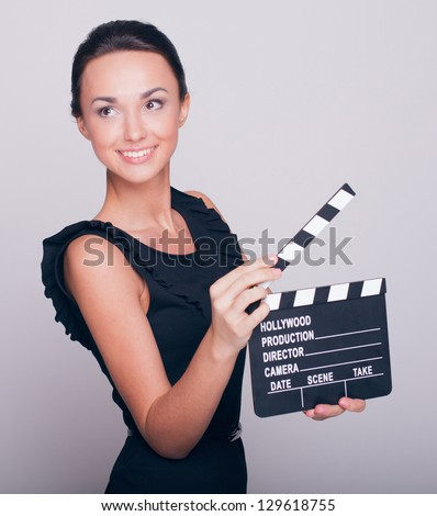 An attractive young woman holds an open film slate - stock photo