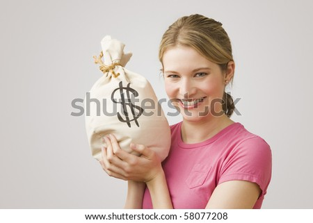 An attractive young woman holds up a bag of money while smiling at the camera.  Horizontal shot. - stock photo