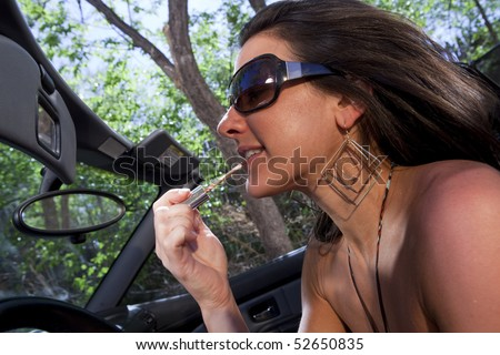 An attractive young woman in a convertible applying lipstick in the rear view mirror while driving. Horizontal shot. - stock photo