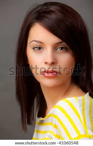 An attractive young woman in a yellow and white striped top. - stock photo
