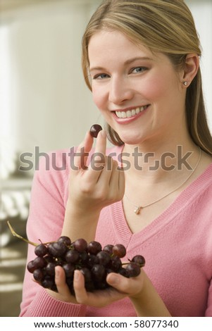 An attractive young woman is eating grapes while smiling at the camera.  Vertical shot.