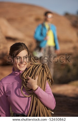 An attractive young woman is holding a rope in preparation for rock climbing. A man can be seen in the background. Vertical shot. - stock photo