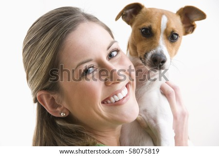 An attractive young woman is looking over her shoulder and smiling while holding a dog. Horizontal shot.