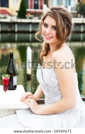 An attractive young woman is smiling and wearing formal attire while sitting at a dockside table with an alcoholic beverage. Vertical shot. - stock photo