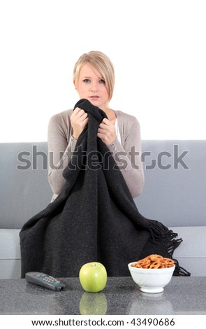 An attractive young woman is watching a thrilling movie at home