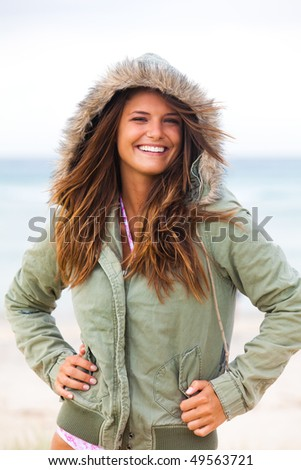 An attractive young woman is wearing a coat at the beach and standing with her hands on her hips. Vertical shot. - stock photo