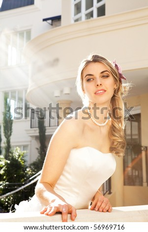 An attractive young woman is wearing a white dress and pearls and is smiling. She is looking over a railing. Vertical shot. - stock photo