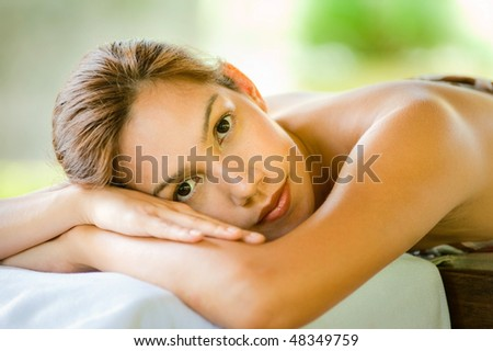 An attractive young woman lying on a massage bed at a spa outdoors - stock photo