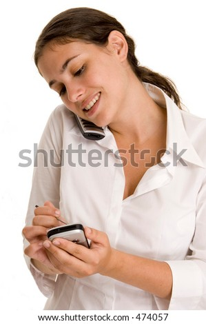 An attractive young woman makes notes on her PDA whilst on the phone - stock photo