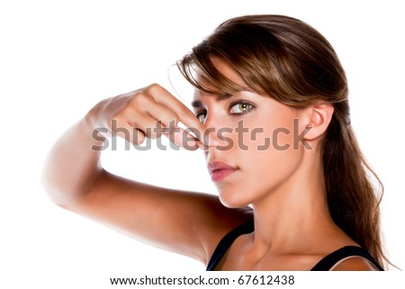 An attractive young woman pinches her nose because something smells