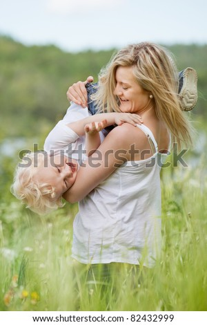 An attractive young woman playing with sweet little boy in green meadow - stock photo