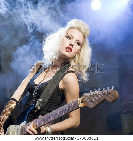 An attractive young woman plays guitar on a stage with lights shining through smoke behind her./Female musician - stock photo