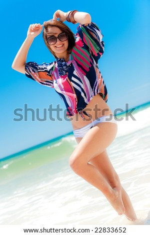 An attractive young woman posing on the beach - stock photo