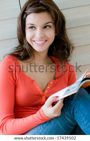 An attractive young woman reading her magazine