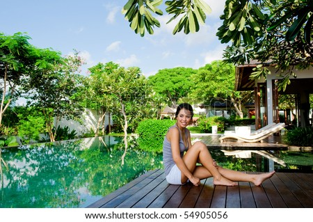 An attractive young woman relaxing outdoors by the pool