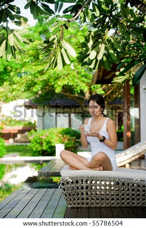 An attractive young woman relaxing outdoors with a drink - stock photo
