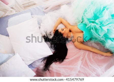 An attractive young woman sits on a bed in a dress fashion - stock photo