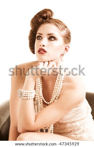 An attractive young woman sitting in a brown leather chair. She is wearing white lace lingerie with pearls. Vertical shot. - stock photo