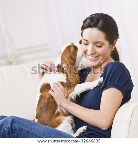 An attractive young woman sitting on a couch and being kissed by a dog that she is holding.  She is smiling and her eyes are closed. Square framed photo. - stock photo