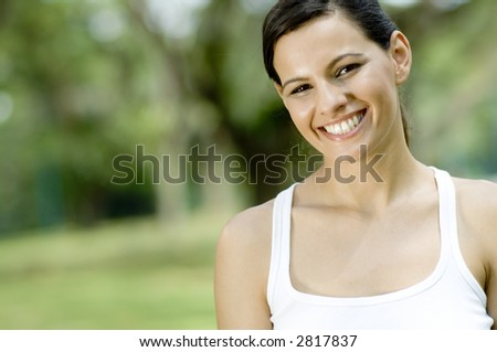 An attractive young woman standing in a park (shallow depth of field used)
