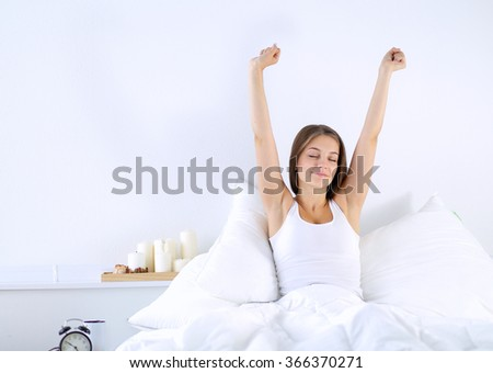 An attractive young woman stretching in bed after waking up - stock photo