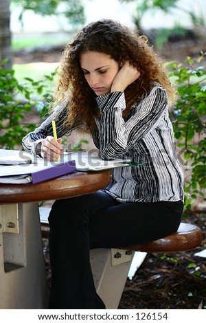 An attractive young woman studies her notes between college classes. - stock photo