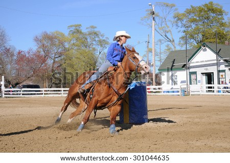 An attractive young woman turns around a barrel and begins racing to the finish line - stock photo