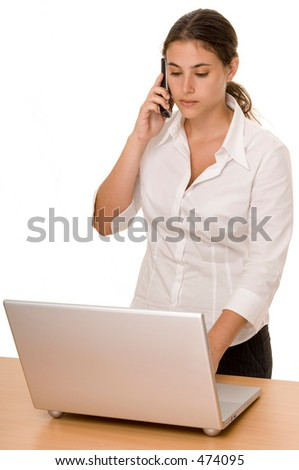 An attractive young woman types on a laptop computer whilst on the phone