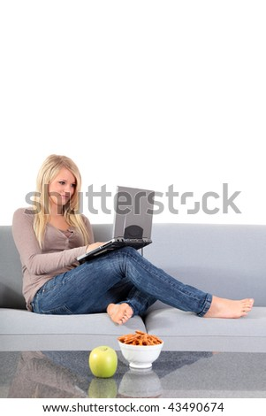An attractive young woman using her notebook computer while sitting on a couch.