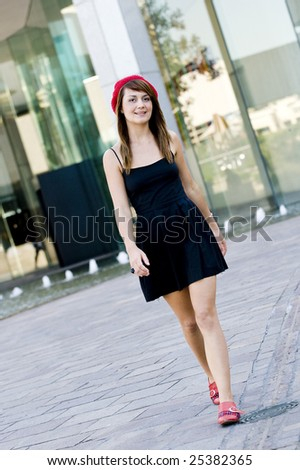 An attractive young woman walking in the city - stock photo