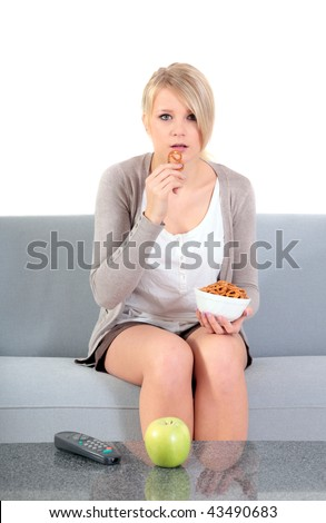 An attractive young woman watching tv an d eating snacks while sitting on a couch.