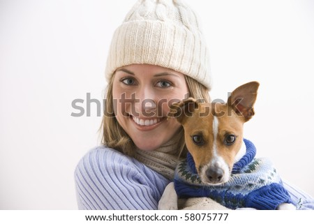 An attractive young woman wearing a knit cap and holding her terrier. Both are wearing sweaters. Horizontal shot.