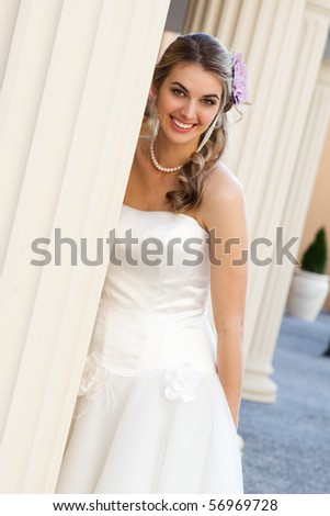 An attractive young woman wearing a white dress and pearls is smiling and standing behind a pillar. She has a purple flower in her hair.  Vertical shot. - stock photo