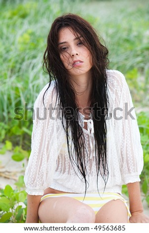 An attractive young woman wearing a white lace top is sitting in the grass at the beach. Vertical shot.