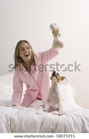 An attractive young woman wearing pink pajamas is holding a dog toy and playing with her terrier on a bed. Vertical shot. - stock photo