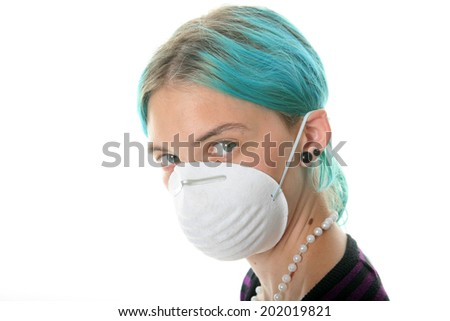 an attractive young woman wears a paper face mask to protect herself from the H1N1 Virus, or any unseen air born virus's or cooties.  isolated on white, with room for your text  health care  - stock photo