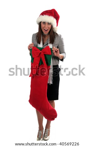 an attractive young woman wears a santa hat and holds a giant christmas stocking, isolated on white - stock photo