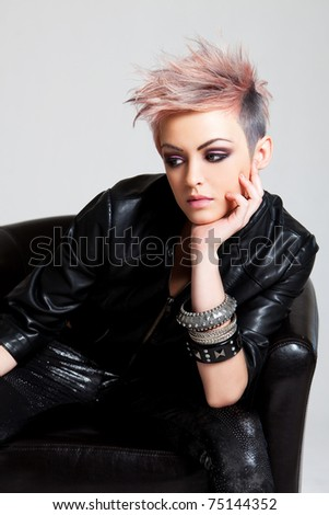 An attractive young woman with a serious expression is sitting in a chair and wearing punk attire. Vertical shot. - stock photo