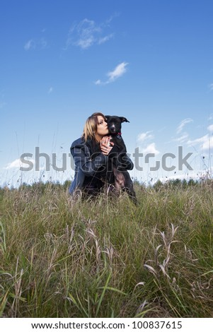 An attractive young woman with her black puppy in a field of long grass and sky. - stock photo