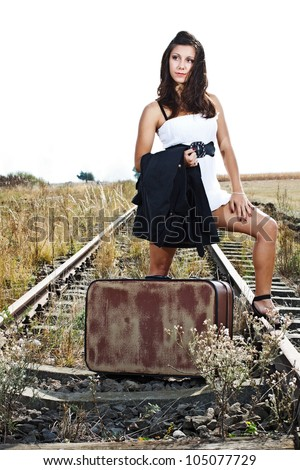 An attractive young woman with long brown hair, wearing white mini dress, standing on railroad with an old suitcase - stock photo