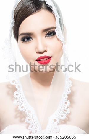 An attractive young woman with makeup on her face. Romantic young woman. Portrait of girl with dark hair on a white background. Beautiful bride with veil. Wedding hairstyle - stock photo