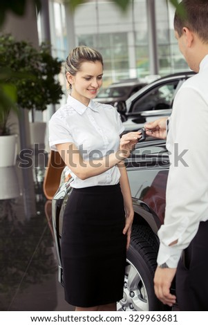 An attractive young woman with the keys to the car - stock photo