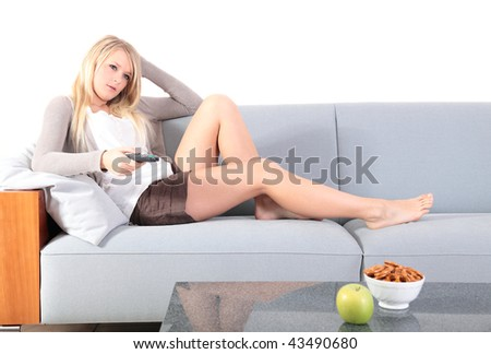 An attractive young woman zapping through boring tv channels