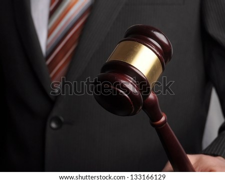 an auctioneer's hand is holding a wooden gavel - stock photo