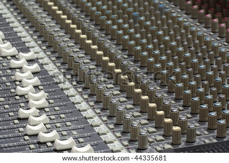 An audio mixer is an electronic device that channels incoming audio signals while maintaining control over such effects as volume level, tonality, placement, and other dynamics for music production - stock photo