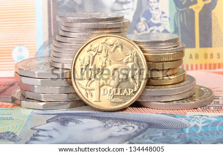 An Australian gold one dollar coin sits next to a stack of coins on top of Australian bank notes.